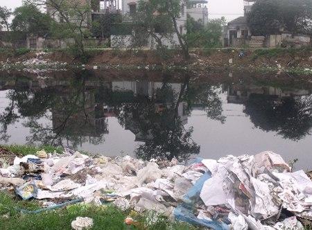 Công nhân vệ sinh môi trường nhặt rác nổi trên sông Tô Lịch